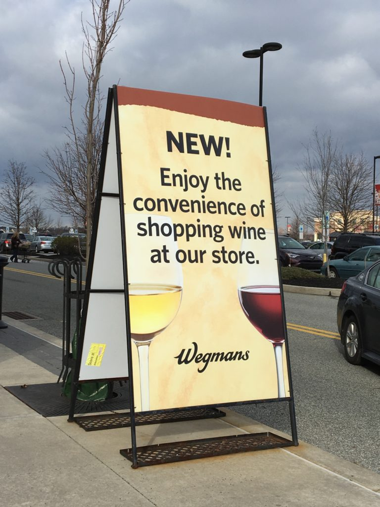 "A-frame sign at a Wegman's supermarket that reads"" New! Enjoy the convenience of shopping wine at our store""."